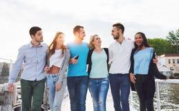 Portrait des jeunes et heureux au repos sur le pilier Amis appréciant un jeu sur le lac Émotions positives Images libres de droits