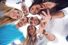 Portrait des jeunes et heureux au repos sur le pilier Amis appréciant un jeu sur le lac Émotions positives Image stock