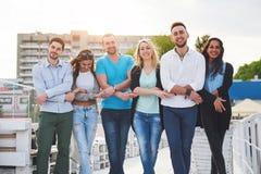 Portrait des jeunes et heureux au repos sur le pilier Amis appréciant un jeu sur le lac Émotions positives Photo libre de droits