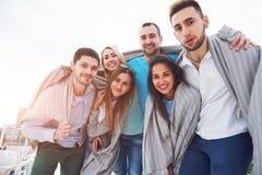 Portrait des jeunes et heureux au repos sur le pilier Amis appréciant un jeu sur le lac Émotions positives Image libre de droits