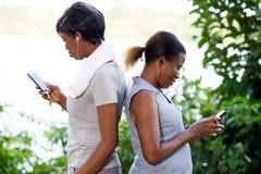 Portrait des jeunes femmes avec des téléphones portables photographie stock libre de droits