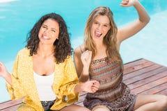 Portrait des jeunes femmes ayant l'amusement près de la piscine image libre de droits
