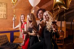 Portrait des jeunes femmes bien habillées attirantes avec des verres de boissons alcoolisées riant ayant l'amusement à la partie  Photos libres de droits