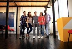 Portrait des jeunes heureux lors d'une réunion regardant l'appareil-photo et le sourire Jeunes concepteurs travaillant ensemble s Images stock