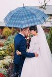 Portrait des jeunes mariés de nouveaux mariés avec le parapluie vérifié dans le jardin d'agrément Photo libre de droits