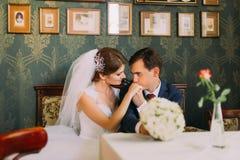 Portrait des jeunes mariés de nouveaux mariés se reposant à la table en café après leur mariage Image stock