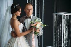 Portrait des jeunes mariés le jour du mariage Le marié dans un costume gris tient la jeune mariée dans un luxe blanc Images stock