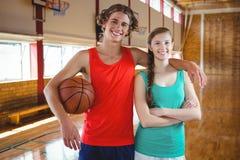 Portrait des joueurs de basket se tenant avec le bras autour Image stock