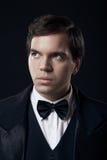 Portrait des jungen Mannes im Smoking getrennt auf Dunkelheit stockfotografie
