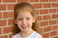 Portrait des jungen Redheadkindmädchens durch Backsteinmauer lizenzfreie stockbilder