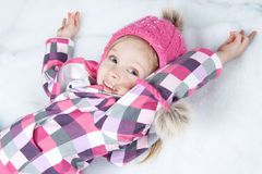 Portrait des kleinen glücklichen Mädchens, das auf Schnee liegt Lizenzfreie Stockfotografie