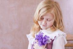 Portrait des kleinen hübschen Mädchens mit Blumen Stockfoto