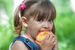 Portrait des kleinen Mädchens, das den Apfel im Freien isst Lizenzfreies Stockbild