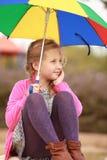 Portrait des kleinen Mädchens mit einem Farbenregenschirm Lizenzfreie Stockfotos