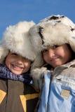 Portrait des kleinen Mädchens und des Jungen in der Pelzschutzkappe Stockfotos