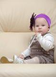 Portrait des Kleinkindes auf dem Stuhl, der eine Spitze anhält Lizenzfreie Stockfotos