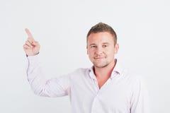 Portrait des lächelnden jungen Kerls, der aufwärts zeigt Lizenzfreies Stockfoto