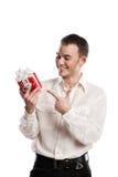 Portrait des lächelnden Mannes zeigend auf Geschenk auf Weiß lizenzfreies stockbild