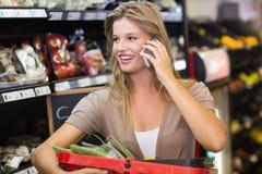 Portrait des légumes de achat de sourire et de téléphoner de femme blonde Image libre de droits