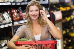 Portrait des légumes de achat de sourire et de téléphoner de femme blonde Photographie stock libre de droits