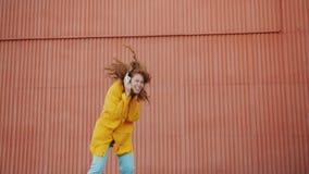 Portrait des lustigen Mädchens im Regenmanttanz im Freien, das Musik in Kopfhörern genießt stock footage
