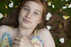 Portrait des Mädchens legend auf Gras und Blumenblätter Stockbilder