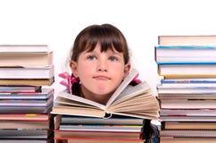 Portrait des Mädchens sitzend unter Stapeln Büchern Stockfotografie