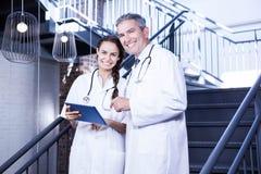 Portrait des médecins heureux tenant le comprimé numérique sur l'escalier photographie stock libre de droits