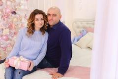 Portrait des ménages mariés contre lesquels pose et se repose sur le plancher Photographie stock libre de droits
