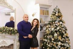 Portrait des ménages mariés posant contre les WI décorés de cheminée Photo stock