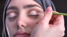 Portrait des mains femelles dessinant l'oeil-flèche rose avec la petite brosse pour la belle femme musulmane dans le hijab sur le banque de vidéos