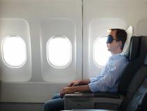 Portrait des Mannes entspannend im Flugzeug Lizenzfreie Stockfotografie