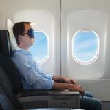 Portrait des Mannes entspannend im Flugzeug Stockfoto
