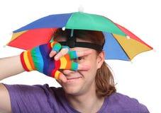 Portrait des Mannes mit Regenbogenhutregenschirm Lizenzfreie Stockbilder