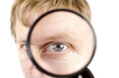 Portrait des Mannes schauend durch ein Vergrößerungsglas Lizenzfreie Stockfotos