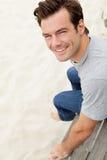 Portrait des Mannes sitzend durch Strand Lizenzfreie Stockfotografie