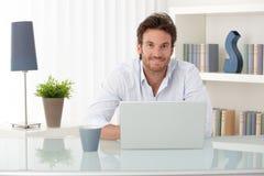 Portrait des Mannes zu Hause mit Computer Stockfotos