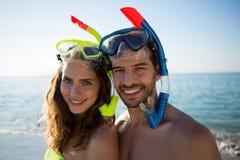 Portrait des masques de port de scaphandre de jeunes couples heureux ensemble à la plage Image libre de droits