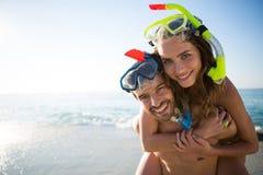 Portrait des masques de port de sourire de scaphandre de jeunes couples ensemble à la plage Photo libre de droits