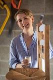 Portrait des meubles mûrs d'Upcycling de femme dans l'atelier à la maison peignant la chaise en bois photos libres de droits