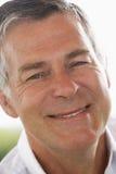 Portrait des mittleren gealterten Mannes, der an der Kamera lächelt Lizenzfreie Stockfotos