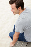 Portrait des mittleren gealterten Mannes, der durch Strand sitzt Lizenzfreies Stockbild