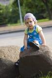 Portrait des nachdenklichen Mädchens sitzend auf einem Felsen Stockfotografie