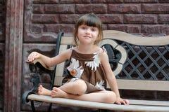 Portrait des netten lächelnden Kindes, das auf Bank sitzt Lizenzfreies Stockfoto