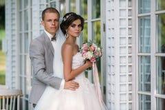 Portrait des nouveaux mariés le jour du mariage Le marié dans un costume gris avec une chemise blanche et un noeud papillon étrei Photo libre de droits