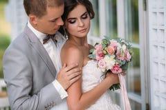 Portrait des nouveaux mariés le jour du mariage Le marié dans un costume gris avec une chemise blanche et un noeud papillon étrei Image libre de droits