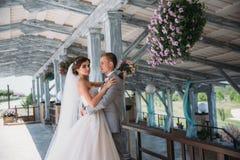 Portrait des nouveaux mariés le jour du mariage Le marié dans un costume gris avec une chemise blanche et un noeud papillon étrei Photo stock