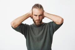 Portrait des oreilles fermantes de beau type barbu nordique avec des mains le montrant à ami mettent le ` t veulent entendre ses  images stock