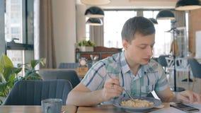 Portrait des pâtes d'eateng de jeune homme et du smartphone d'utilisation en café banque de vidéos
