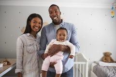 Portrait des parents avec la fille de bébé dans la crèche Image libre de droits